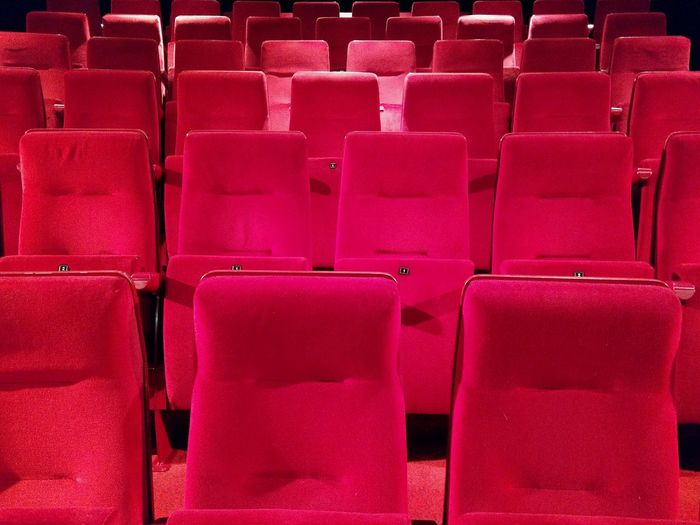 Full frame shot of red empty seats in auditorium