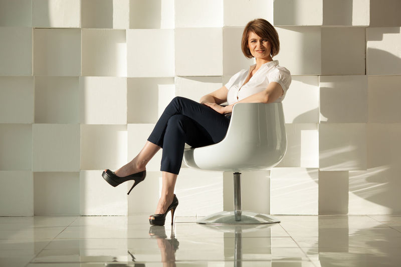 Smiling businesswoman sitting in chair with crossed legs against of white wall made of cubes. Attractive Background Beauty Boss Brunette Business Businesswoman Caucasian Cubes Elegant Fashion Female Horizontal Person Portrait Woman Young Adult Young Women
