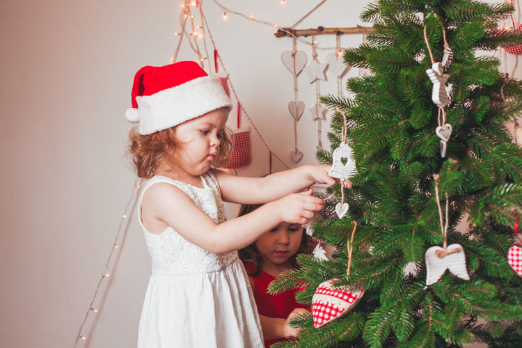 Cute girl decorating christmas tree at home