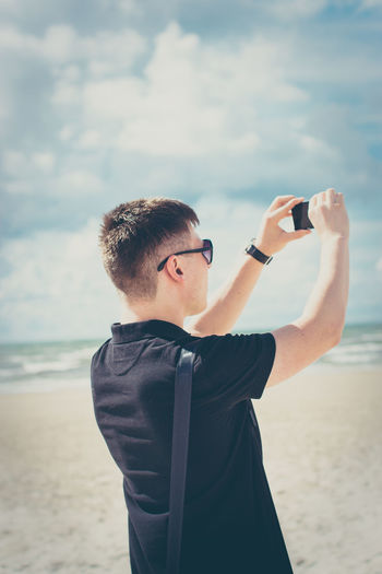 Latvia Liepaja Beach Holding Horizon Over Water Leisure Activity Lifestyles Nature One Person Outdoors Photographing Photography Themes Rare View Real People Sea Sky Standing Summer Technology Tourism Waist Up Water Young Adult Young Man