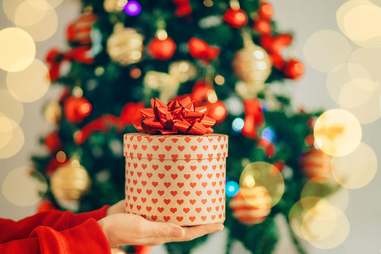 Close-up of hand holding gift against christmas tree at home