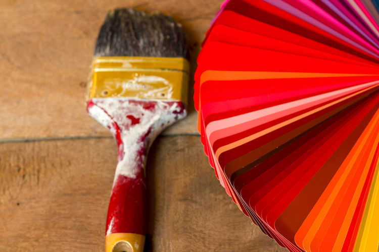 High angle view of paint brush by color swatch on table