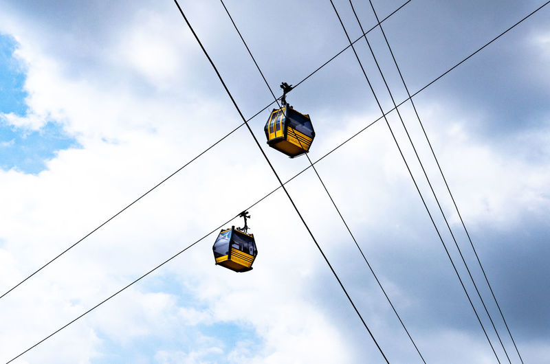 Cable Cable Car Cloud - Sky Connection Day Electricity  Hanging Leisure Activity Low Angle View Mode Of Transportation Nature Outdoors Overhead Cable Car Real People Sky Transportation Travel Yellow The Traveler - 2018 EyeEm Awards