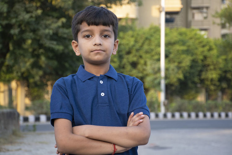 Portrait of boy standing with arms crossed outdoors