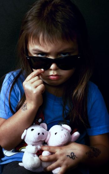 Close-up portrait of girl wearing sunglasses holding stuffed toys