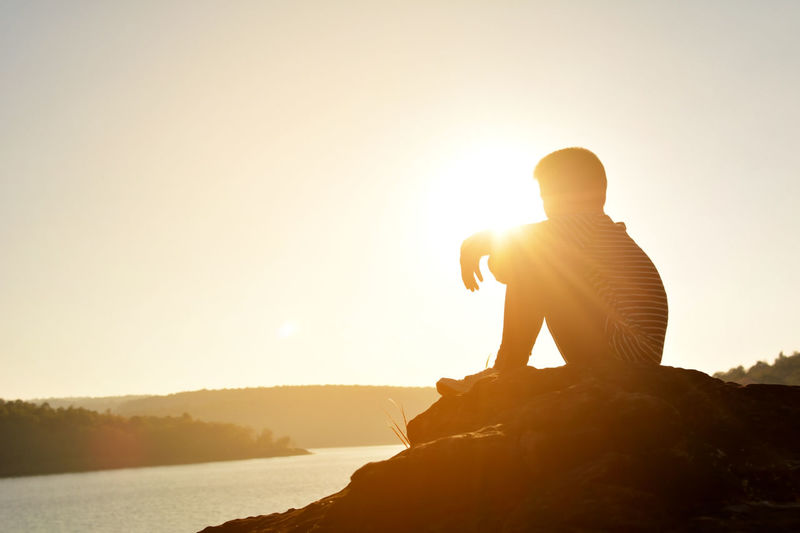 Silhouette Teenage Boy Sitting On Rock Formation By Lake Against Sky During Sunset
