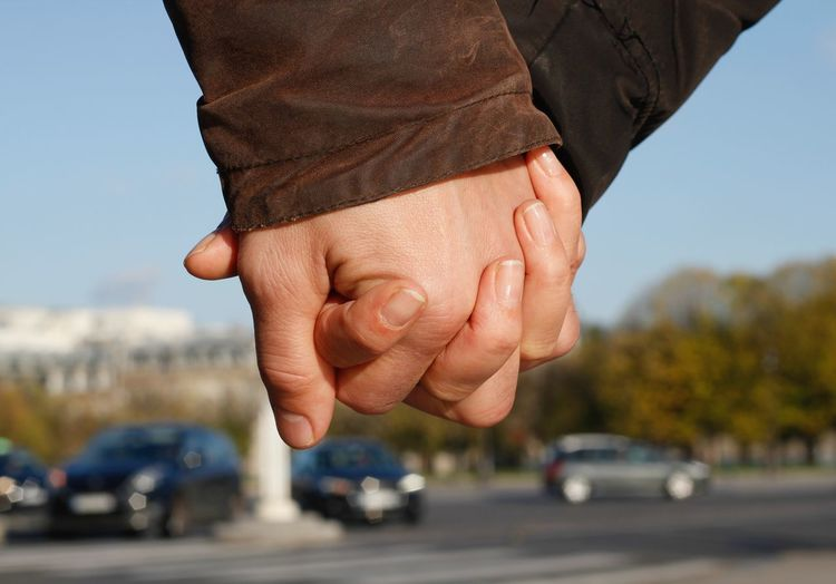 Close-Up Of Couple Holding Hands On Street