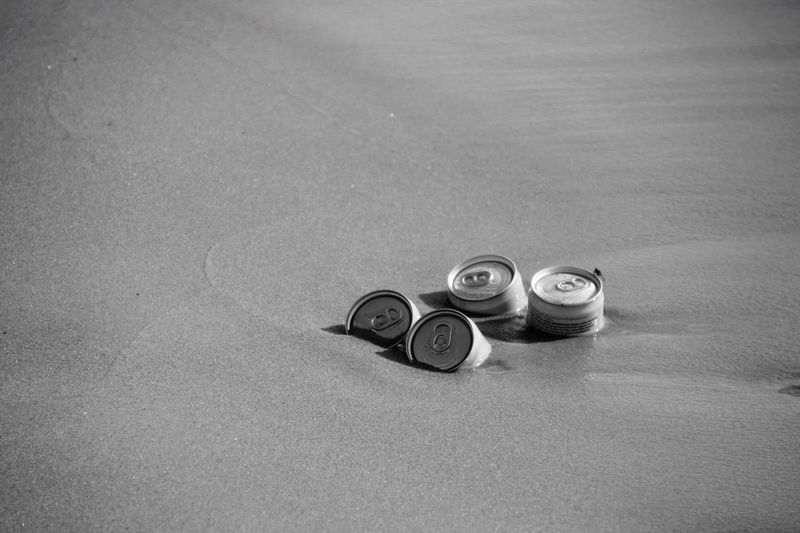 High angle view of drink cans on sand at beach