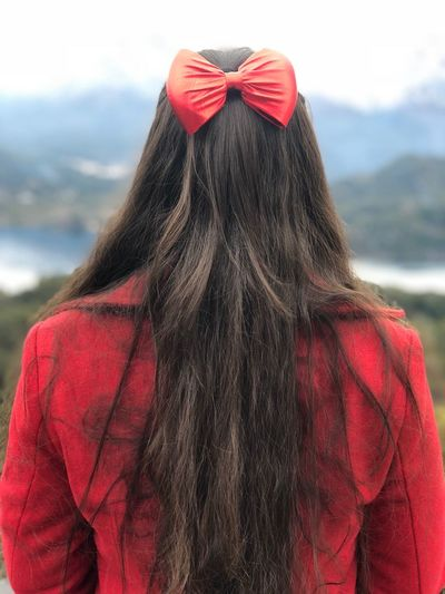 Rear view of woman wearing bow in hair while standing outdoors