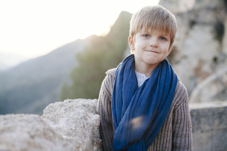blond boy looking at camera at sunset Blond Hair Boys Childhood Close-up Day Elementary Age Focus On Foreground Front View Leisure Activity Lifestyles Looking At Camera Mountain Mountain Range Nature One Person Outdoors People Portrait Real People Smiling Standing Young Adult