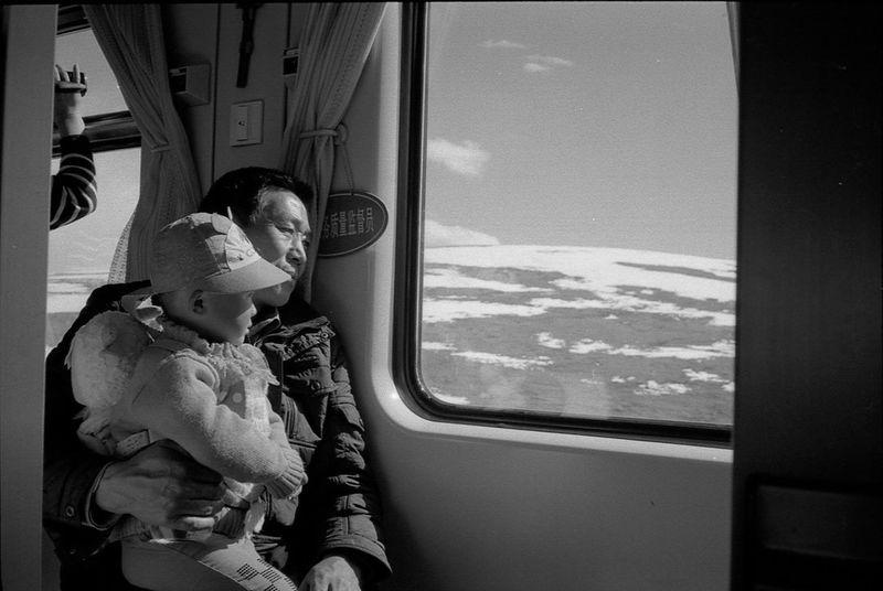 青藏铁路上爷孙俩透过车窗看着自己的家乡青藏高原 Traveling