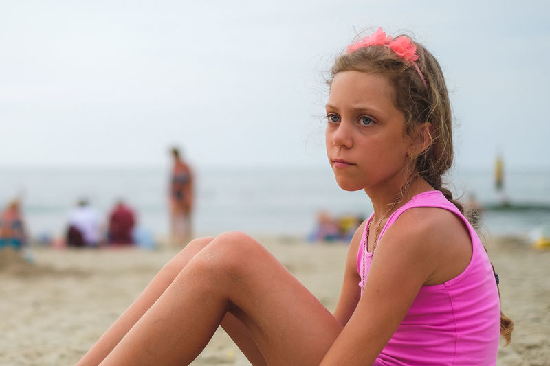 Thoughtful Girl Looking Away While Sitting At Beach
