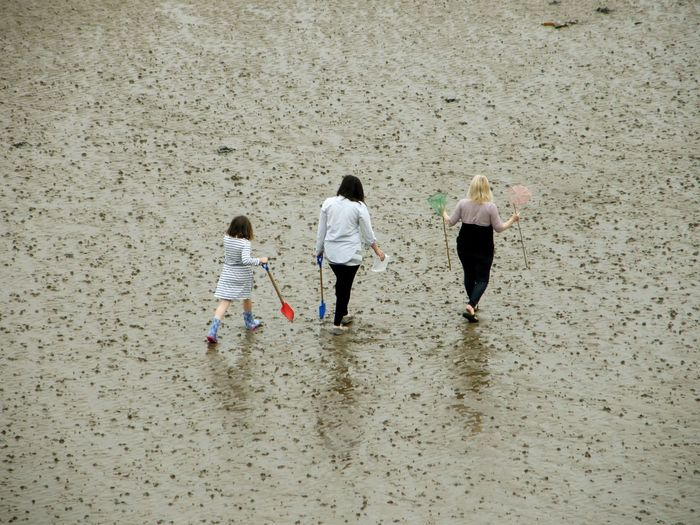 High angle view of women and girl walking at beach