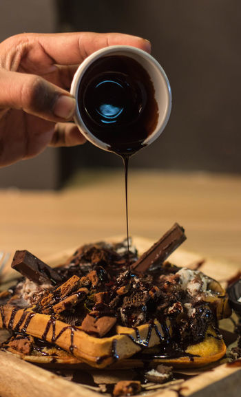 Close-up of hand pouring chocolate syrup on waffle