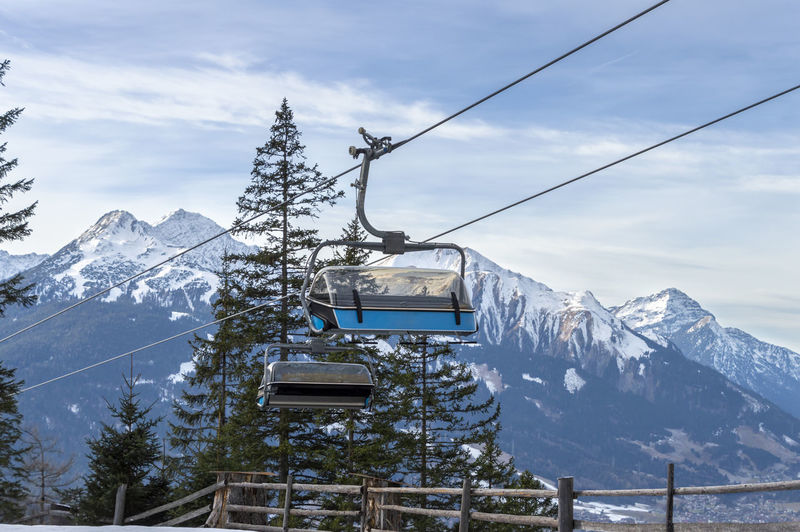 Low Angle View Of Ski Lift Against Snowcapped Mountains