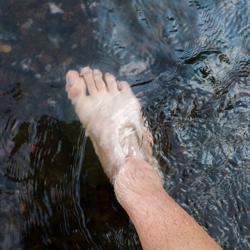 Close up human foot while stand in rapid water stream, relax in shallow creek