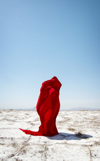 Abstract portrait a body coverd with red fabric in middle of a salt lake