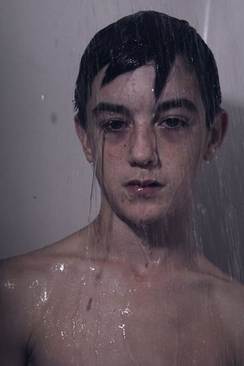 Close-up portrait of teenage boy under shower in bathroom