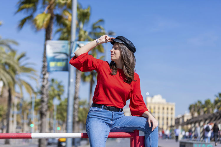 Front view of beautiful young woman wearing casual clothes sitting on a metallic fence outdoors in the city while touching her hat in a bright day One Person Real People Casual Clothing Lifestyles Leisure Activity Three Quarter Length Focus On Foreground Young Adult Young Women Day Red Women Nature Front View Sky Hair Looking Adult Outdoors Hairstyle Beautiful Woman Woman Sitting Smiling Laughing Hat Urban Skyline Brunette Girl Teenager City City Life Cute Cool Modern Denim Jeans