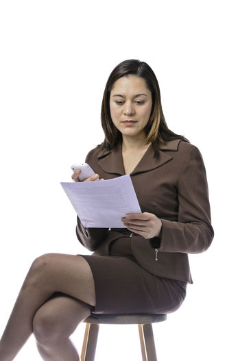 Businesswoman Sitting On Chair Looking At Document Against White Background