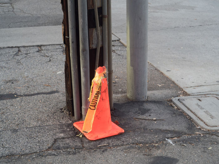 Traffic cone and barrier tape in abandoned situation next to power-line pole City Communication Cone Day Footpath High Angle View Nature No People Orange Color Outdoors Pole Protection Road Safety Security Sidewalk Sign Street Traffic Cone Transportation