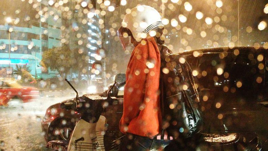 Woman on motor scooter on street seen from wet car window