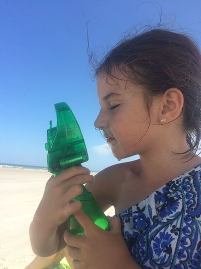 Close-Up Of Girl Spraying Water With Bottle At Beach Against Clear Blue Sky