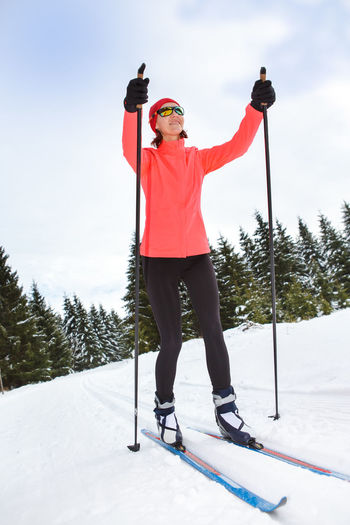 A woman cross-country skiing in the Alps Action, Activity, Adult, Competition, Cross-country, Female, Fit, Fitness, Forest, Healthy, Holidays, Langlauf, Lifestyles, Nordic, People, Running, Skating, Skiing, Snow, Sports, Style, Training, Winter, Woman Arms Raised Cold Temperature Day Front View Full Length Human Arm Leisure Activity Lifestyles Limb Mountain Mountain Range Nature One Person Outdoors Real People Red Sky Snow Sport Standing Warm Clothing Winter