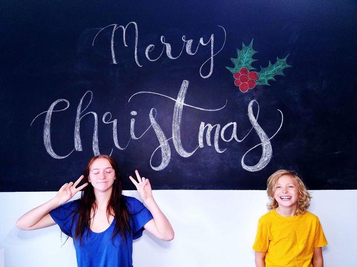 Happy Siblings Against Blackboard During Christmas