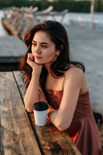 Young woman with coffee while sitting on table
