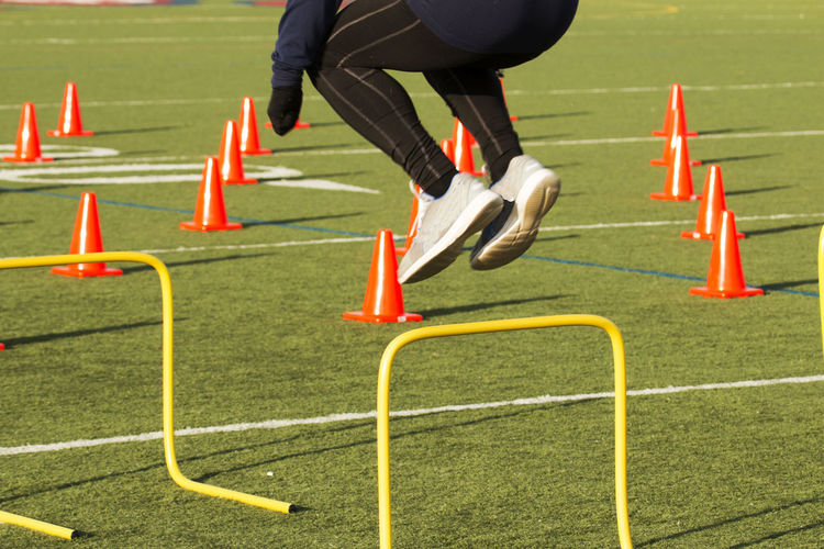 Low section of man jumping over hurdlers