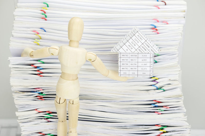 Close-up of wooden figurine holding model house against stacked files over gray background