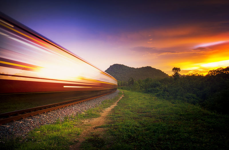 Old train that runs through the countryside, at sundown. Train Fast Speed Green Blue Sky High Concept Track Shipping  Summer Countryside Beautiful Wood Rail Locomotive Electricity  Travel Motion Colorful Blur Tourism Forest Communication Electric Sunset Railway Railroad Tracks Orange Background Landscape Road Sundown Sun LINE Transportation Sunrise Transport Iron Horizon Light Path Fantasy Way