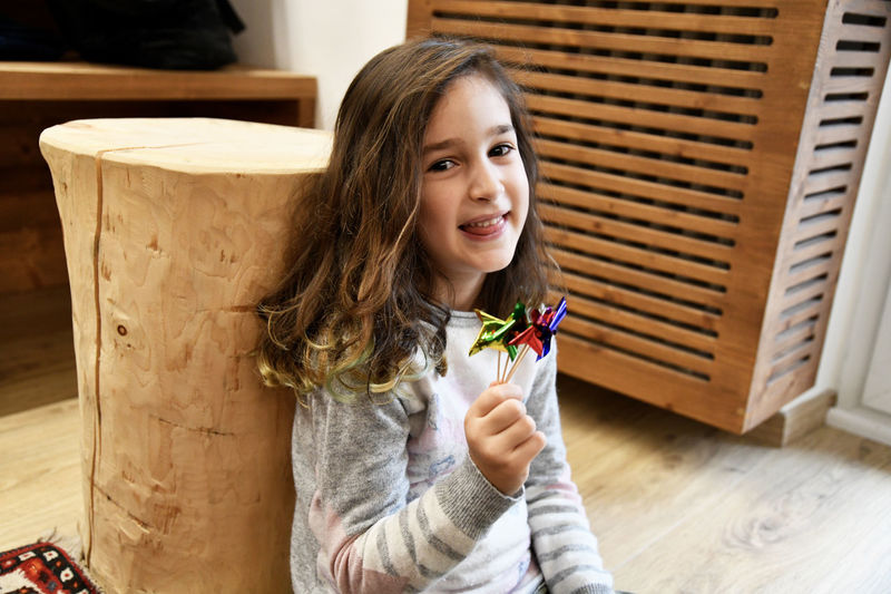 Portrait of smiling girl with pinwheel toys at home