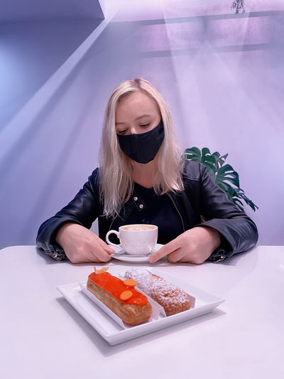 Woman sits in a cafe with a medical mask on her face and looks sadly at a cup of coffee and eclairs.