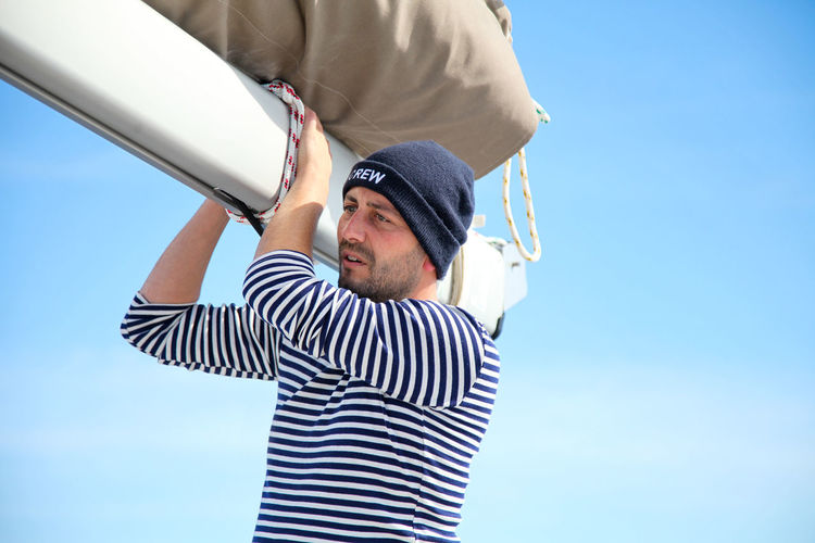 Low angle view of man holding canvas while standing against blue sky