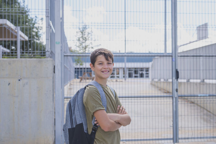 Portrait of smiling boy with arms crossed standing against school