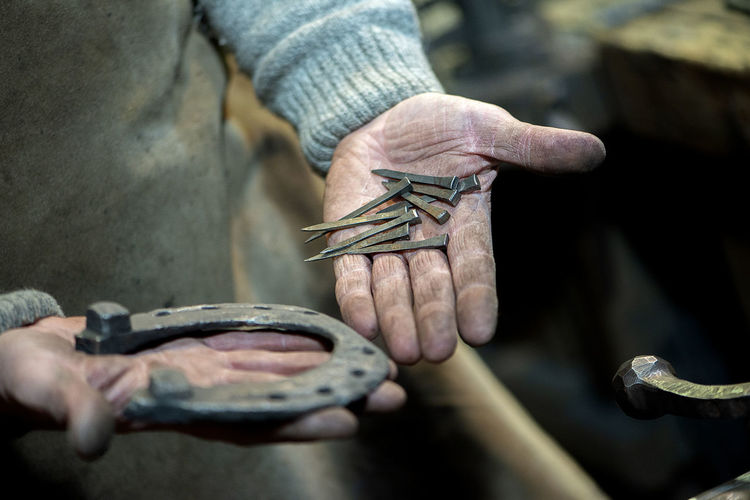 Close-up a dirty blacksmith's hand holds a horse's horseshoe and nails