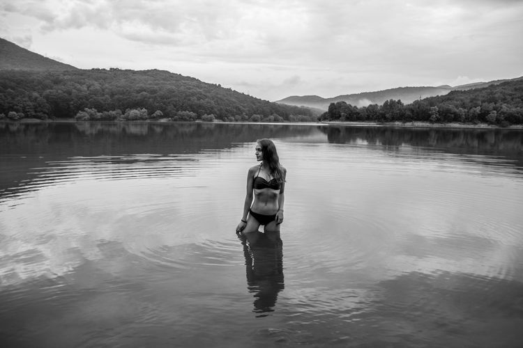 Woman standing in lake against sky