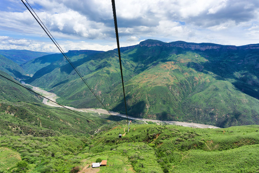 View of the aerial tram in Chicamocha Canyon near Bucaramanga, Colombia Adventure Bucaramanga Cableway Canyon Chicamocha Cliff Colombia Destination Holiday Landmark Landscape Mountain National Park Nature Outdoors Panachi River Rock Santander Scene Tourist Travel Tree Valley View