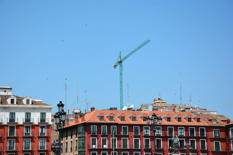 Low angle view of cranes and buildings