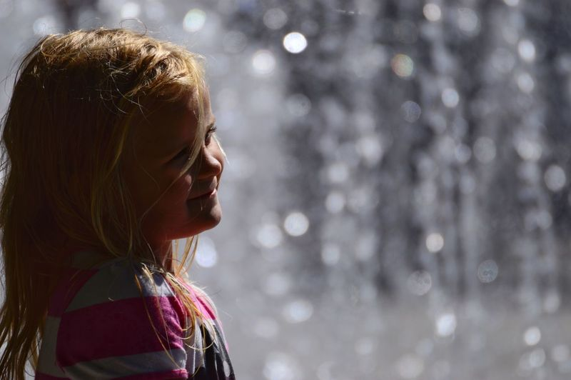Cute girl looking away by fountain