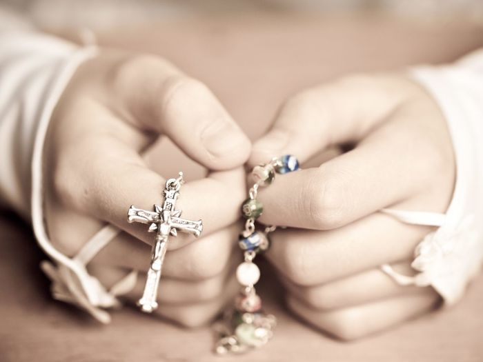 Cropped hands of woman holding rosary