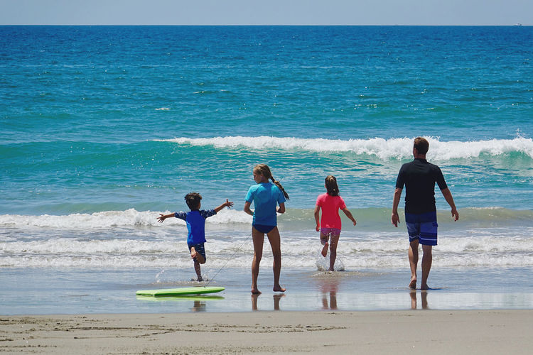 Rear view of daughters with father walking at beach