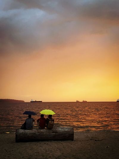 ...and then it began to rain Dramatic Sky People Under Umberella People Together People Umbrellas Rain EyeEm Selects Sky Water Scenics - Nature Beauty In Nature Orange Color Land Horizon Over Water Beach Outdoors Cloud - Sky Horizon