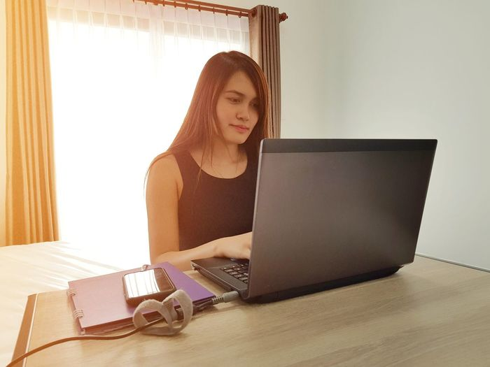Young woman using laptop while sitting at table