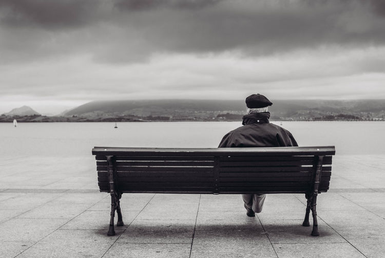 Rear view of man sitting on bench by river against cloudy sky