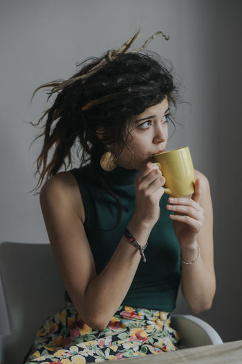 Portrait of a young female model with dreadlocks drinking coffee at home Coffee Tea Beautiful Woman Casual Clothing Dreadlocks Drink Drinking Drinking Glass Food And Drink Front View Glass Hair Hairstyle Hippie Holding Indoors  Leisure Activity Lifestyles Long Hair One Person Real People Refreshment Sitting Women Young Women