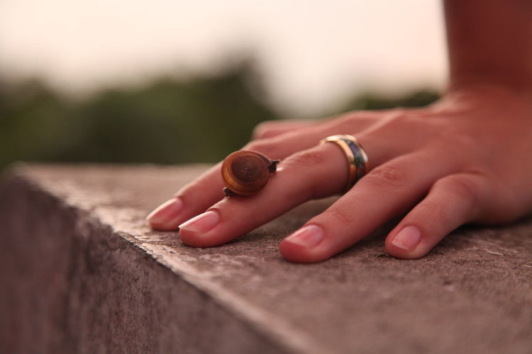 Close-up of woman hand on retaining wall