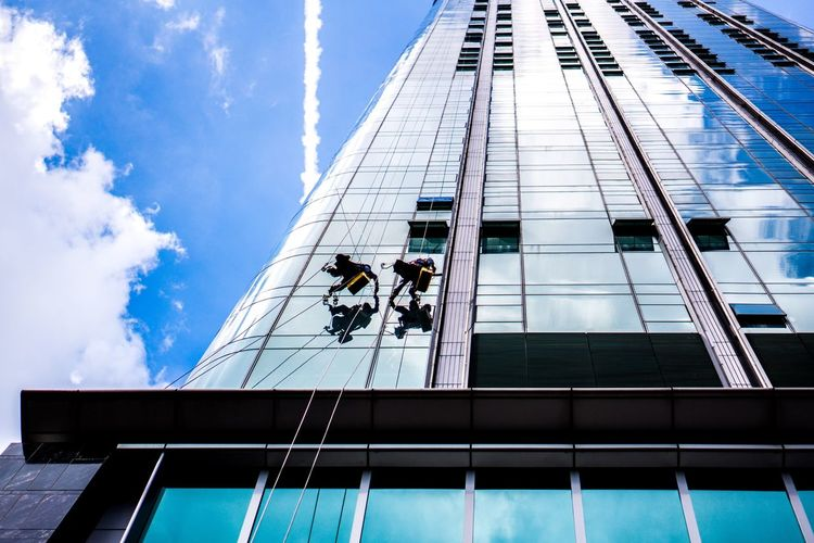 Low angle view of two window cleaners